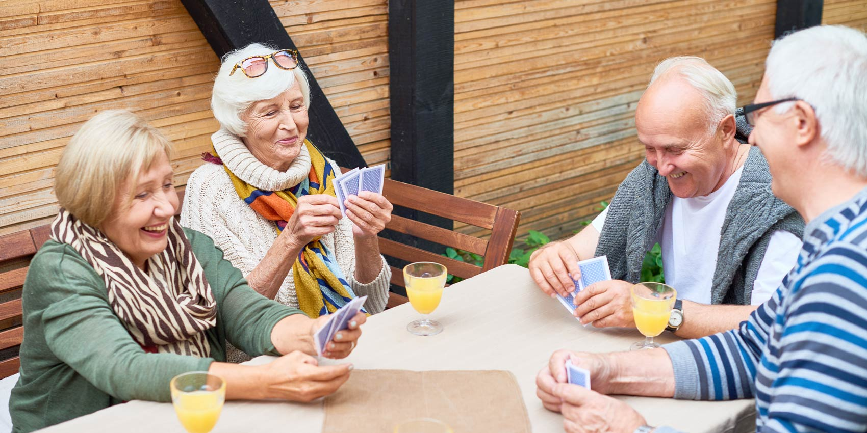Senior friends playing cards outside.