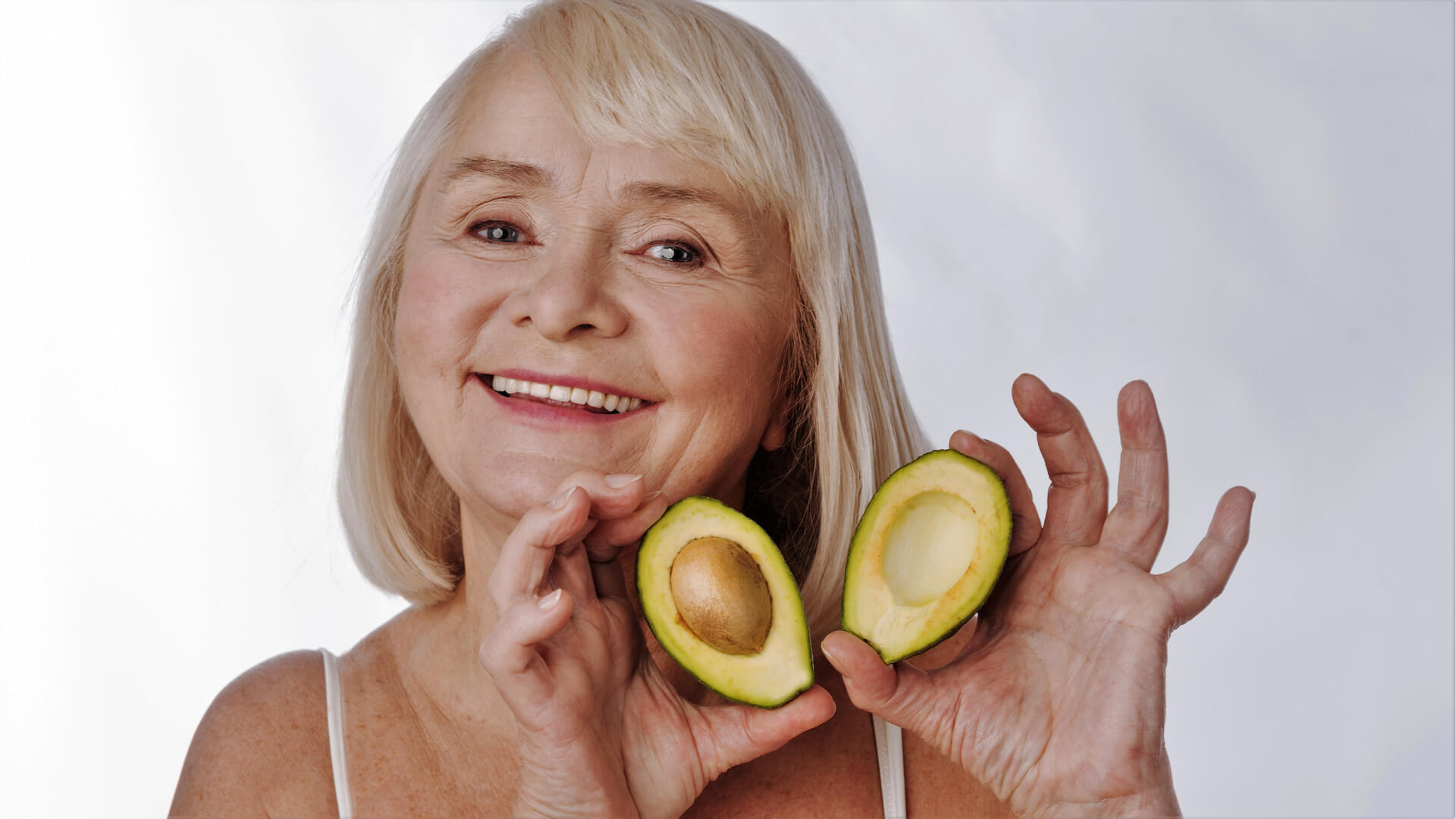 Cheerful happy woman showing you avocado halves