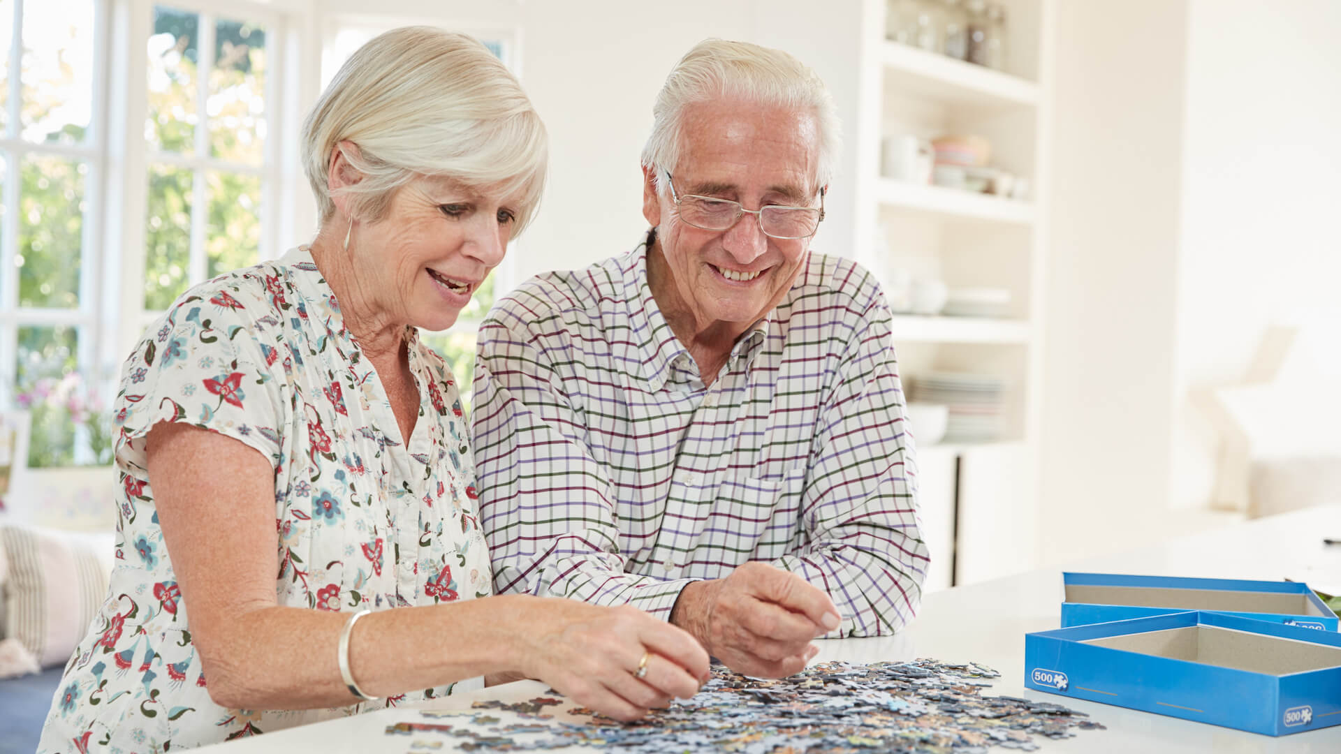 Senior couple doing a jigsaw puzzle at home