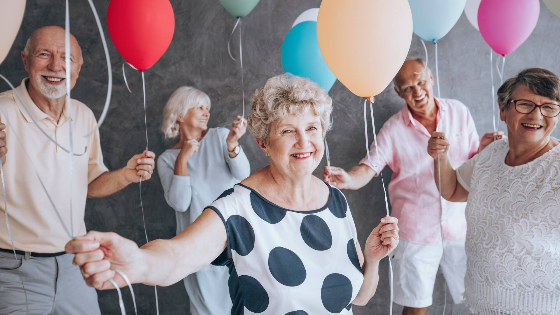 Smiling grandmother wearing a blouse with black dots during New Year's Eve party with friends holding colorful balloons