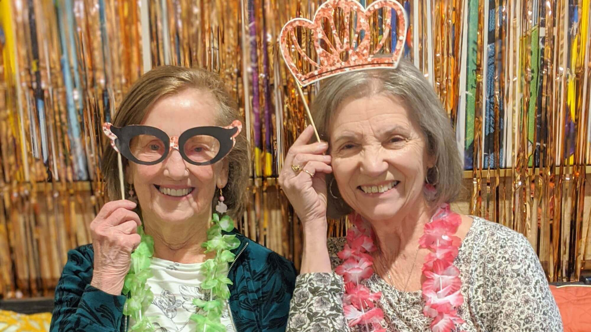 Senior friends having fun with their masks and crowns