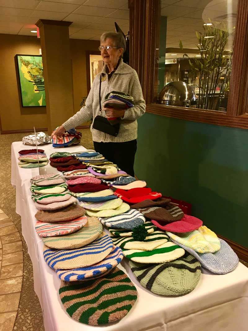 Senior giving away her quilted hats to people in need of them.