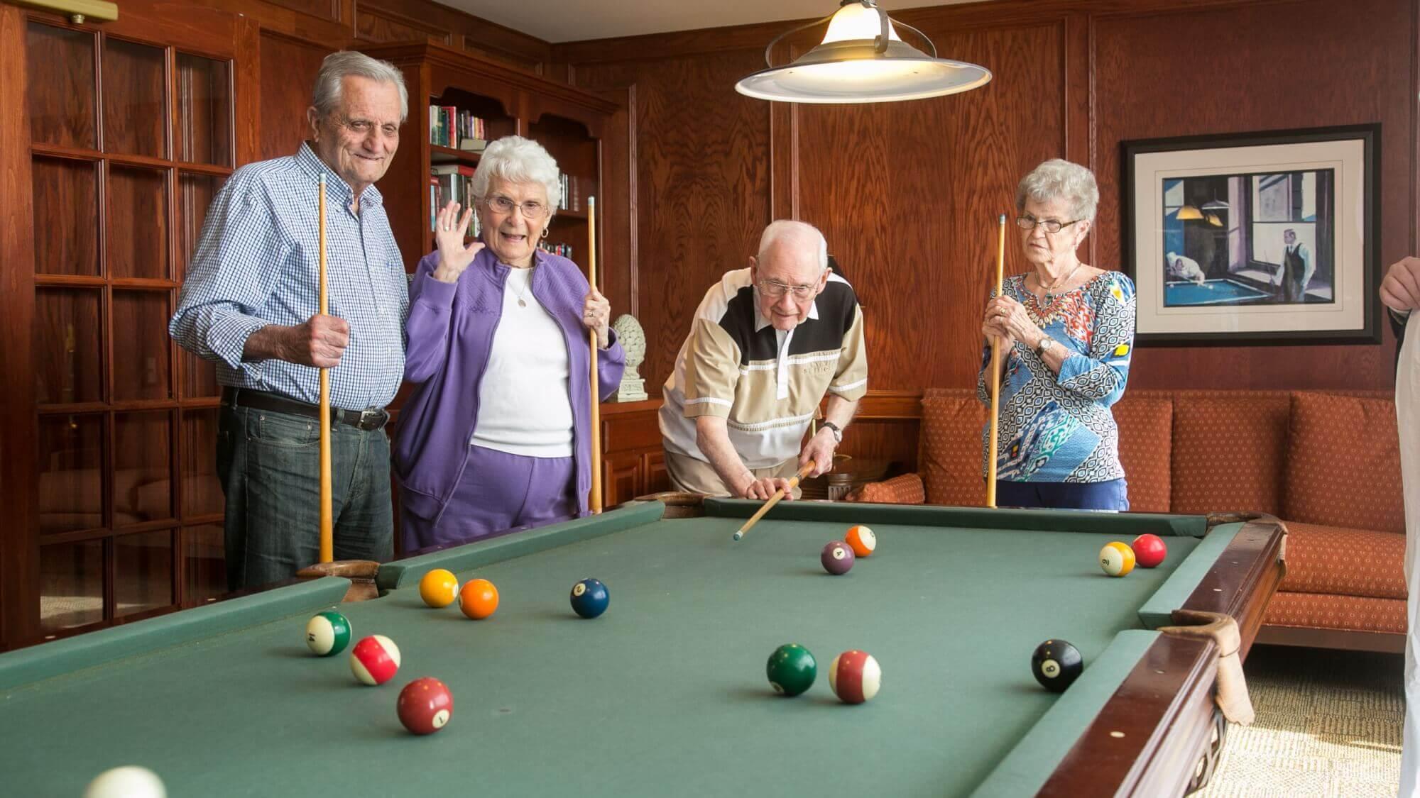 Senior friends playing billiards together celebrating a shot