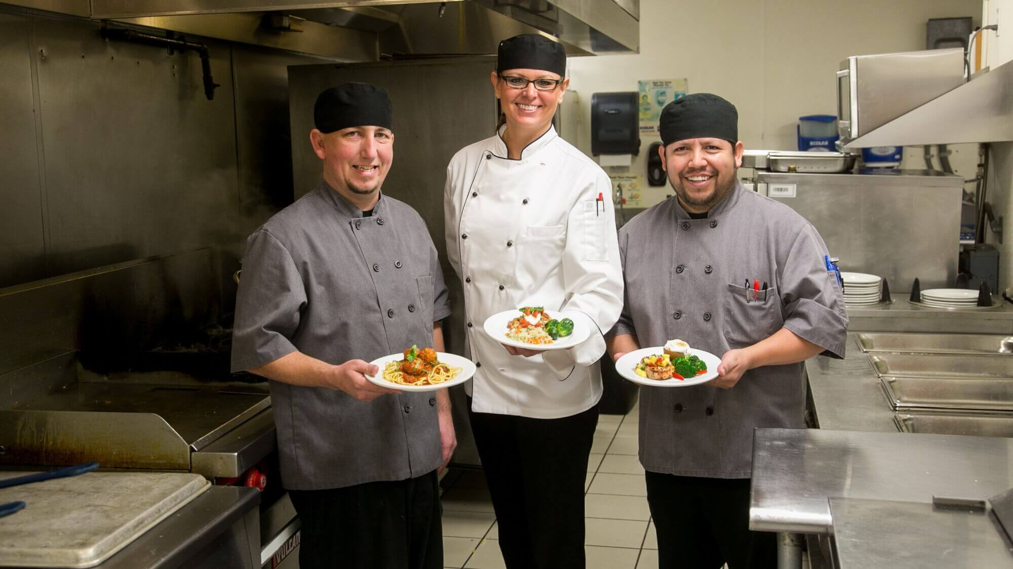 Three culinary teammates, displaying their main dishes that are about to be presented to their residents.