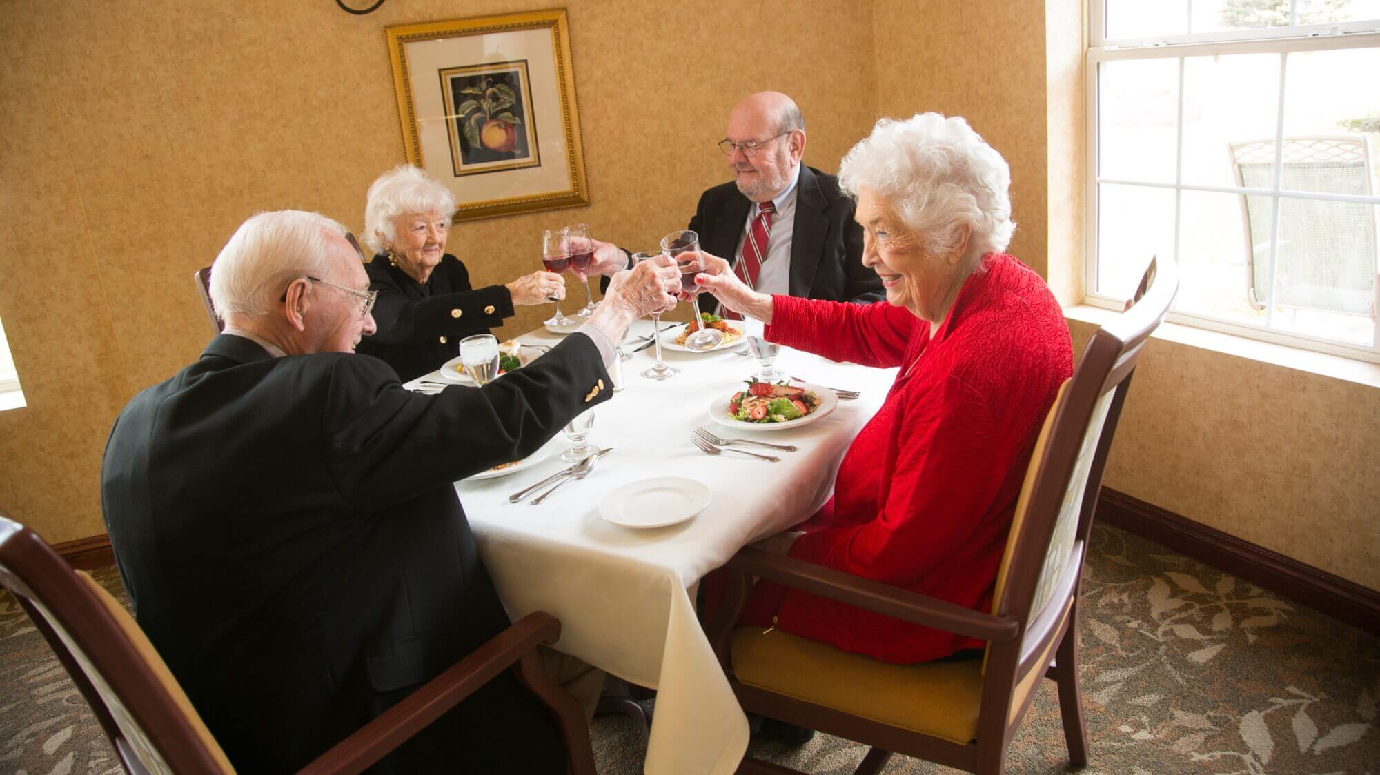 Senior friends dining at the table, cheering their wine glasses together.