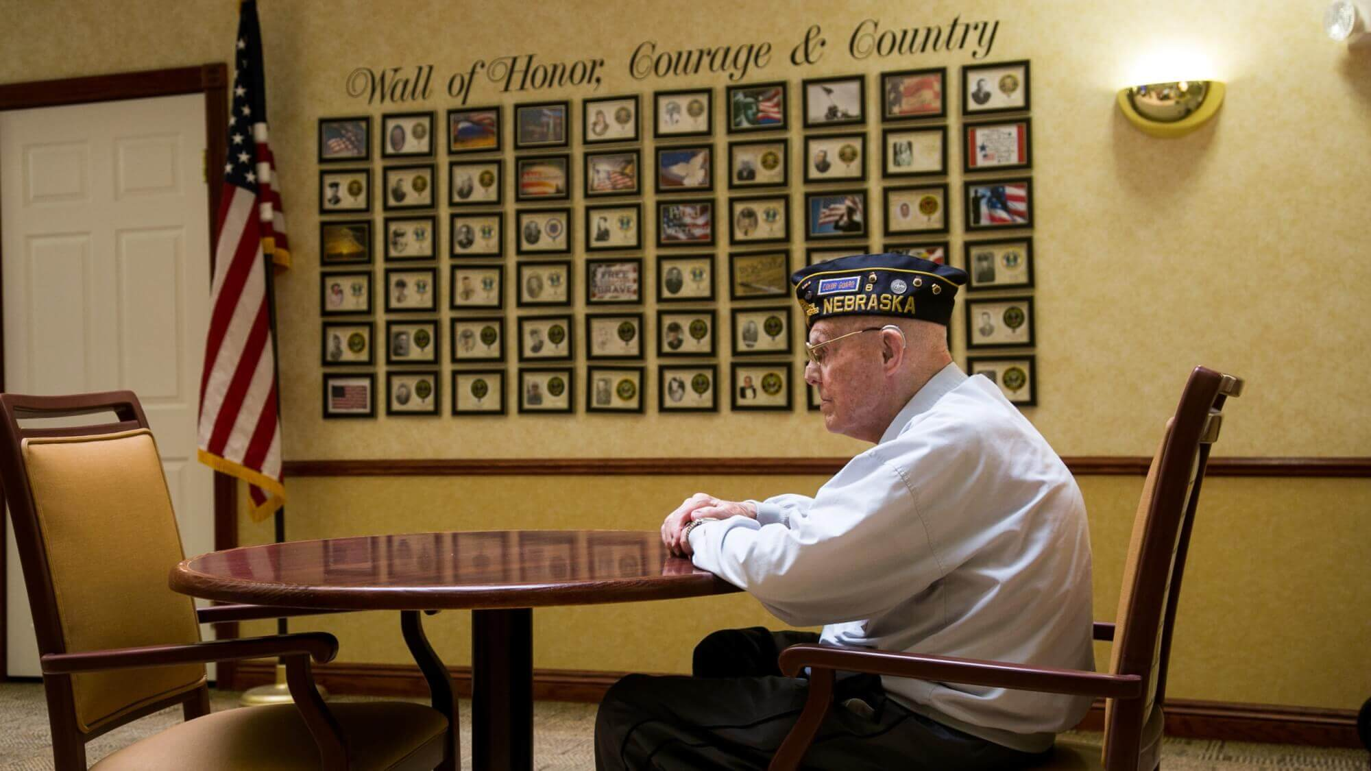 Senior veteran sitting at a table looking in the distance, in front, of the Wall of Honor, Courage and Country.