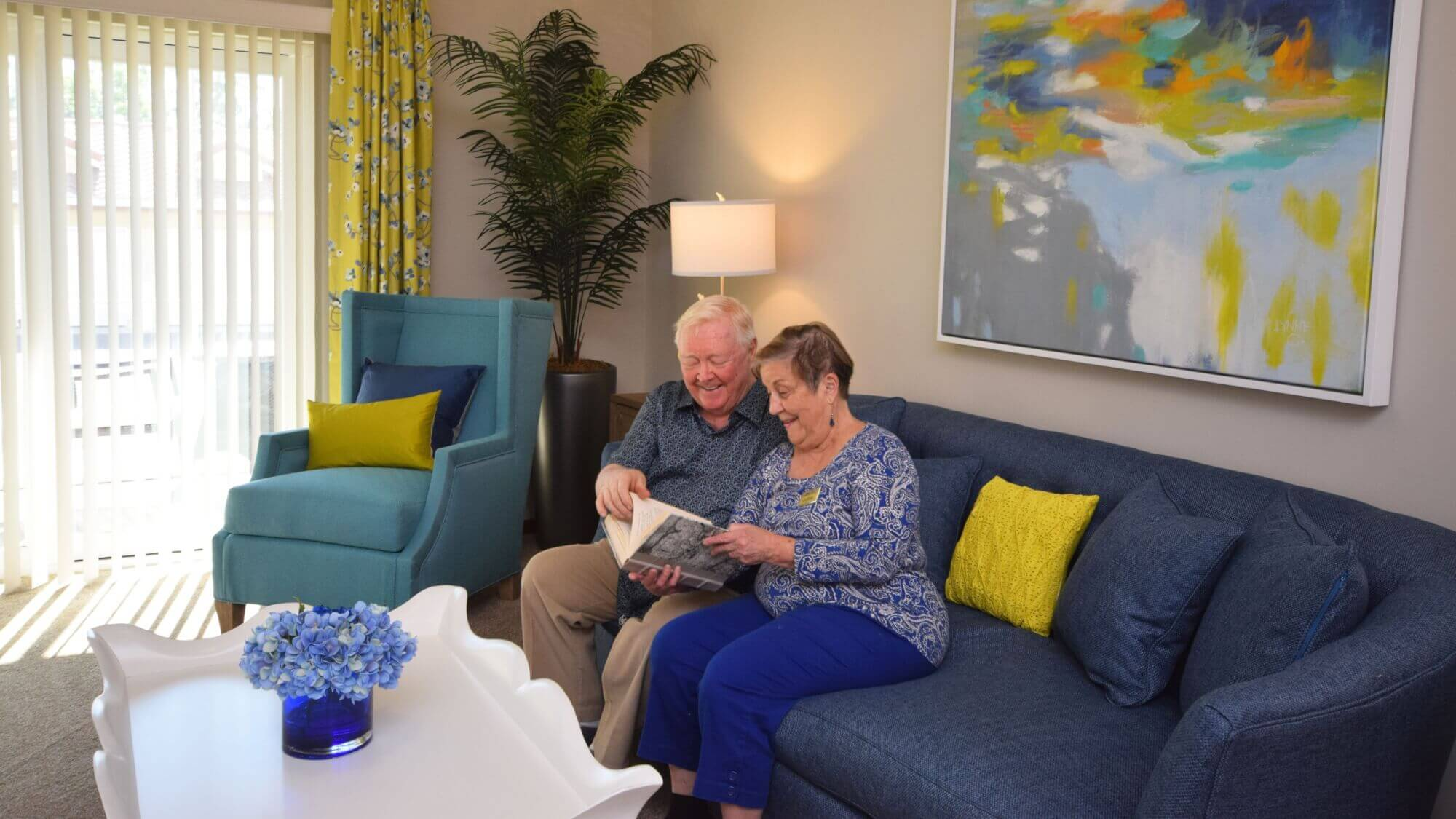 Senior couple sitting on the couch reading a book.