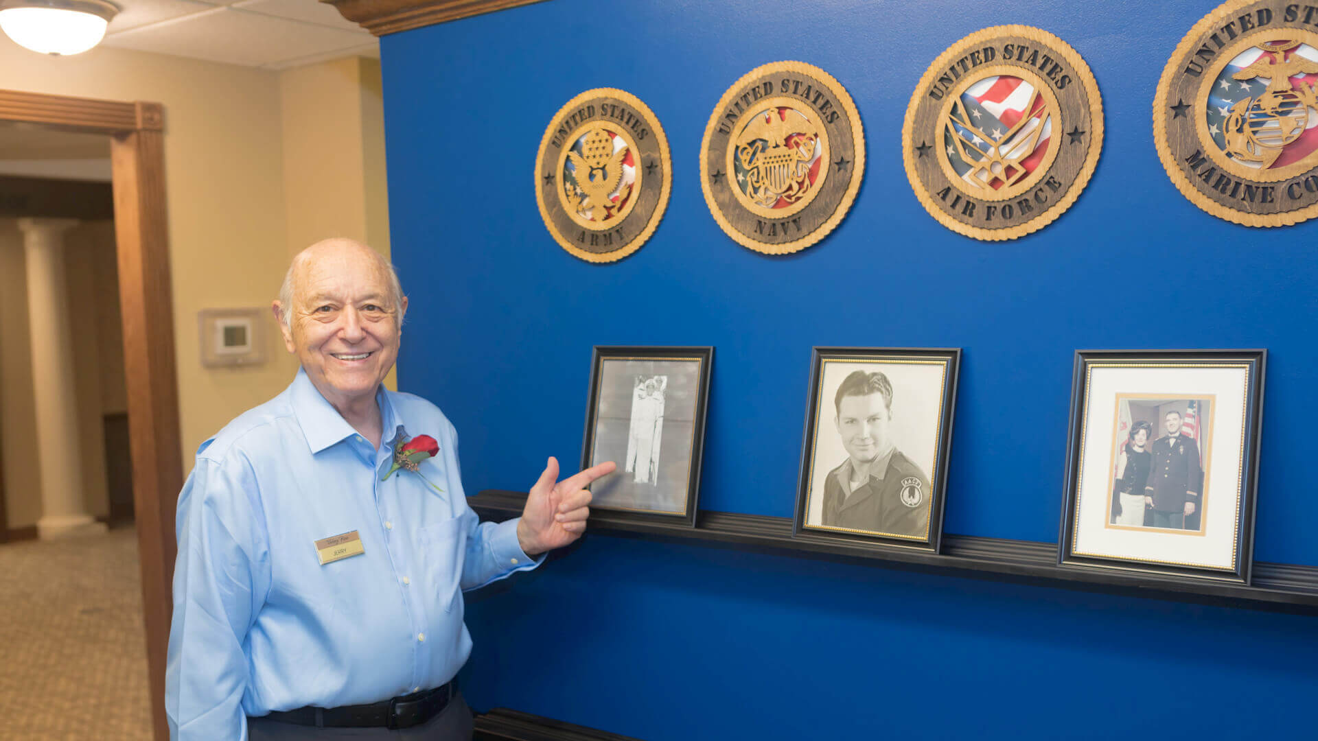 Senior Veteran standing in front of the Wall of Honor, showing off his service picture.