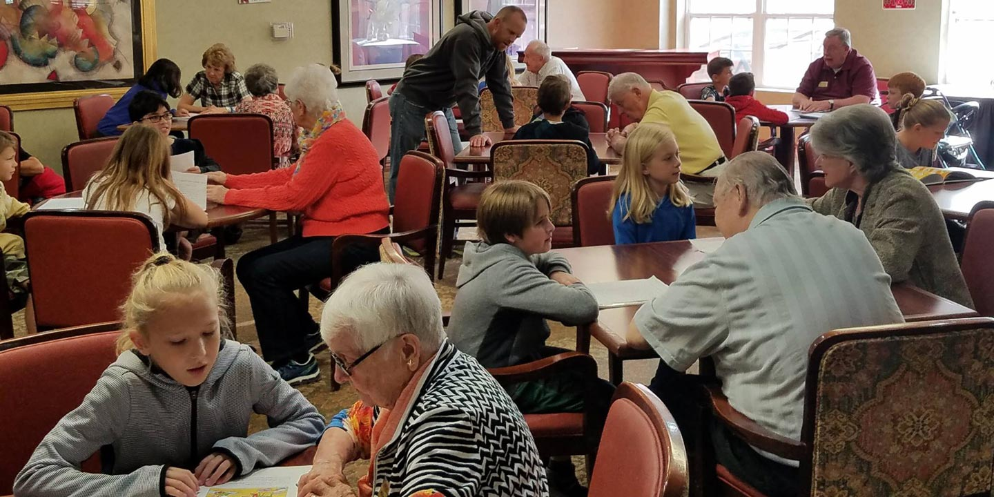 Seniors talking and spending time with young children in a dining room.