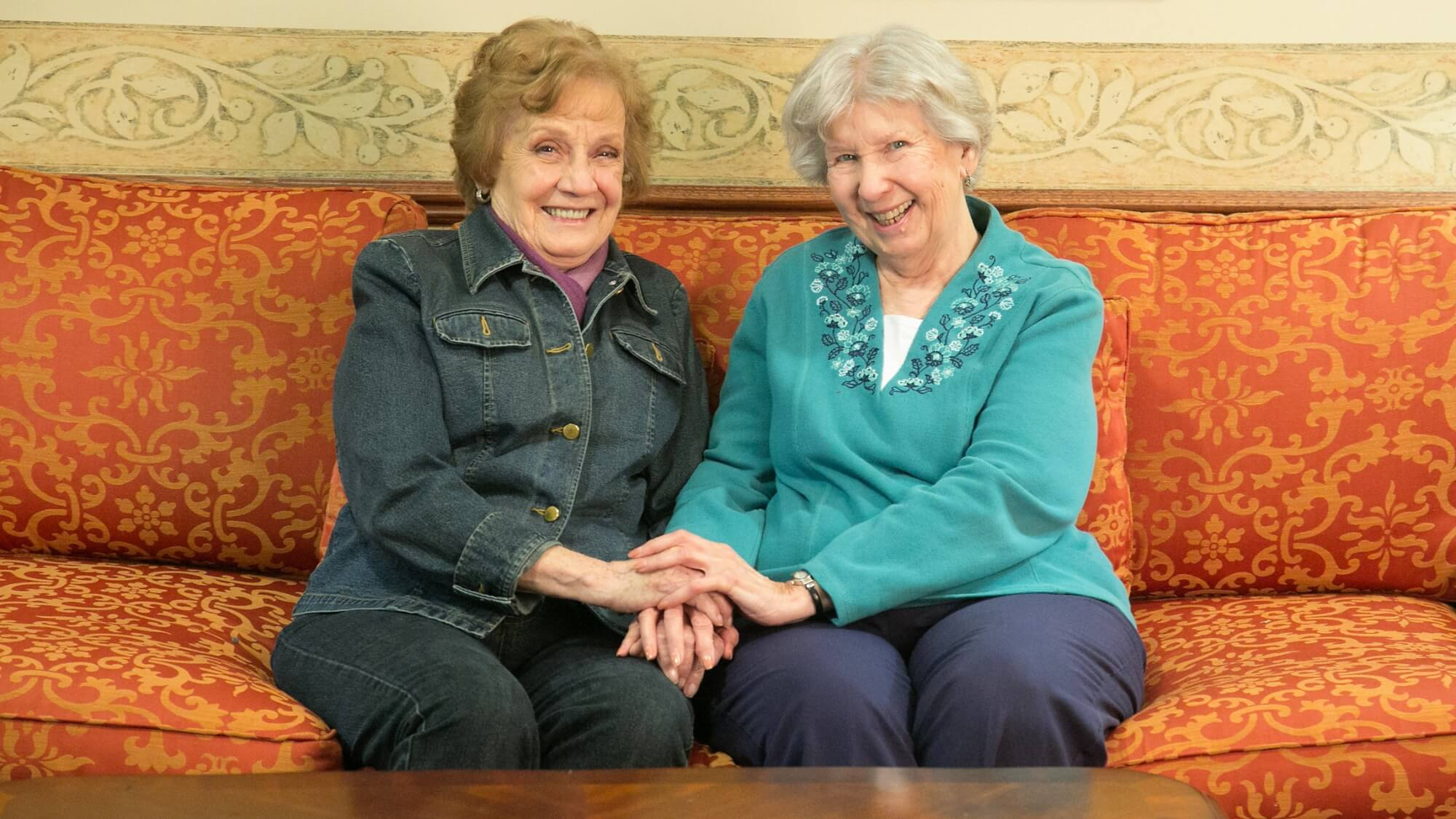 Senior friends sitting on the couch holding hands at Walnut Grove.