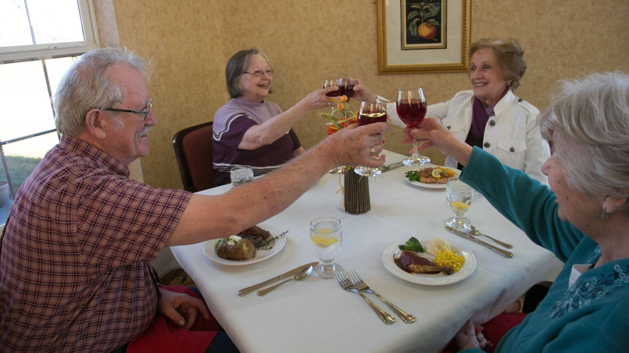 Senior friends dining together, cheering their wine glasses.