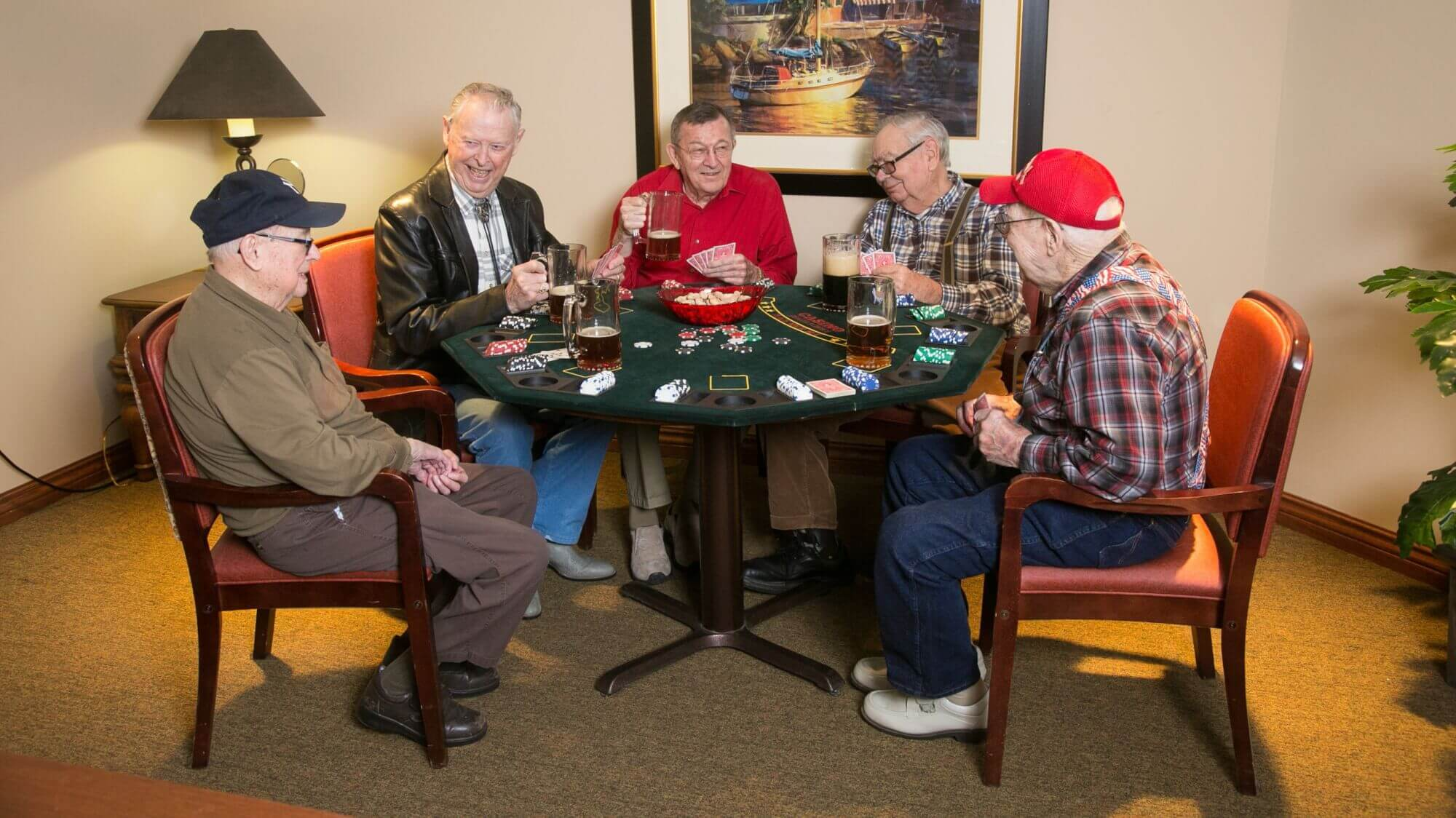 Senior friends playing poker and drinking beer.