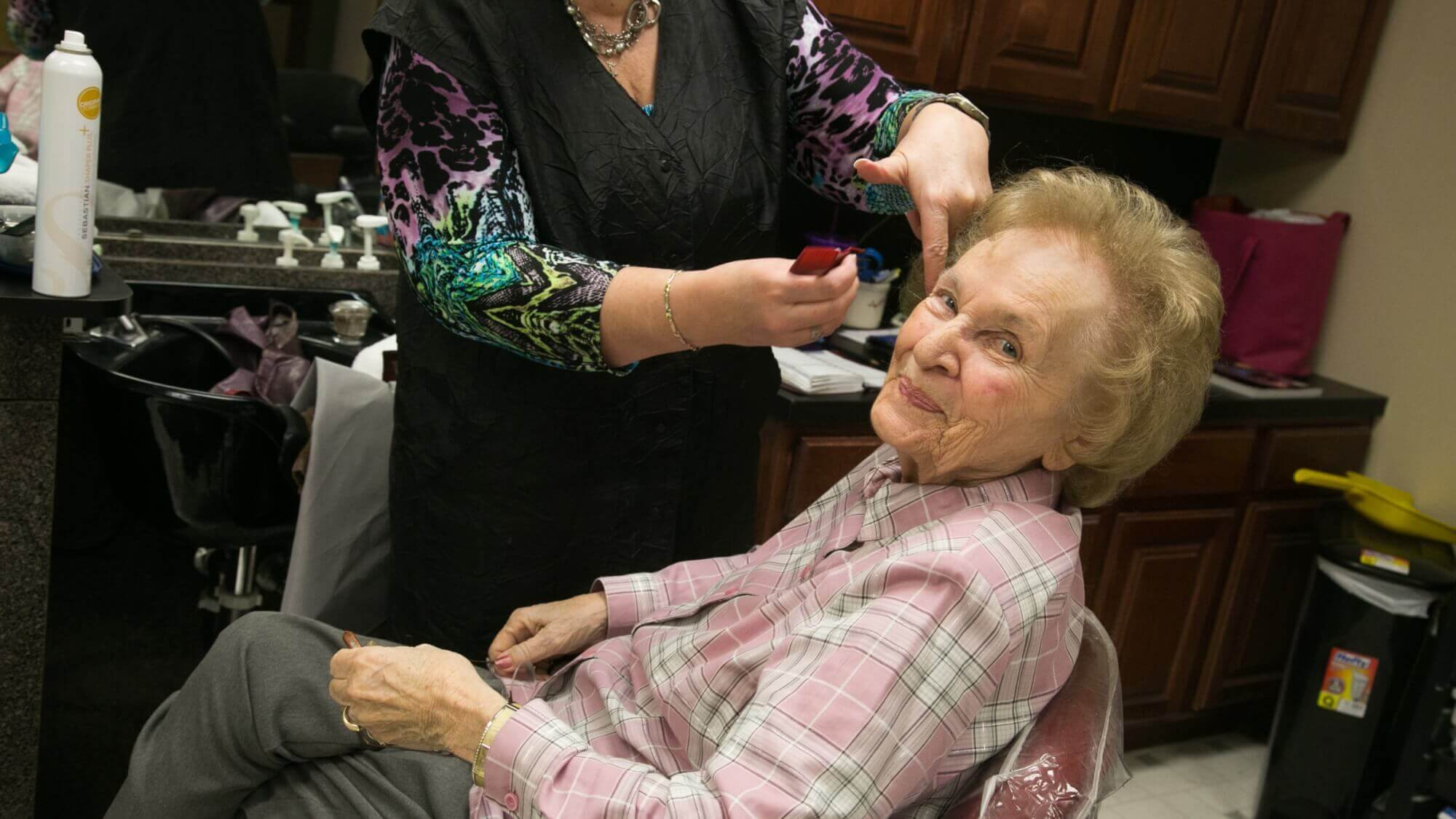 Happy senior receiving a hair cut at Resort Lifestyle Communitites.