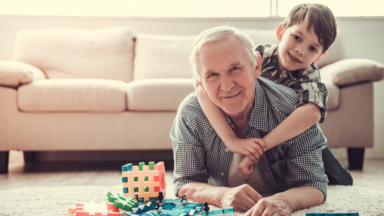 Grandpa playing toys with grandson hugging neck